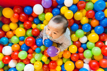 Fototapeta na wymiar Asian baby playing in colorful ball pool
