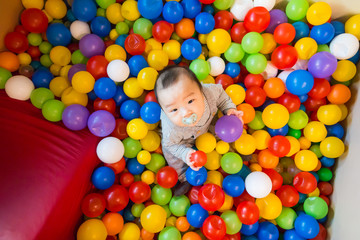 Fototapeta na wymiar Asian baby playing in colorful ball pool