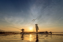 Image Is Silhouette.Asian Fisherman Myanmar On Wooden Boat Fishermen Casting Are Going Out To Fish Early In The Morning With Wooden Boats, Old Lanterns And Nets. Concept Fisherman's Life Style