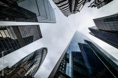 Low angle view of skyscrapers. Looking up perspective. Bottom view of modern skyscrapers in business district. Business concept of success industry - 246426046