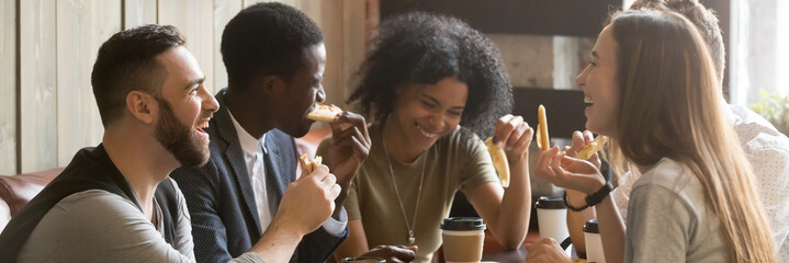 Five friends drinking coffee eating pizza at cafe, diverse people laughing tell jokes having fun in public place, multiracial friendship free time concept, horizontal banner for website header design