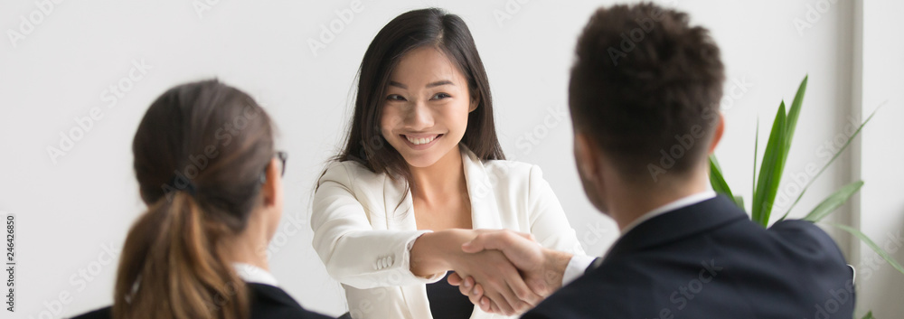 Fototapeta Smiling successful young asian applicant handshake with hr manager feels happy getting hired, boss congratulating employee new job employment concept. Horizontal photo banner for website header design