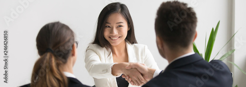 Cuadros en Lienzo  Smiling successful young asian applicant handshake with hr manager feels happy getting hired, boss congratulating employee new job employment concept