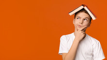 Boy With Book On Head Thinking On Orange Background
