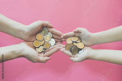 Fotografie, Obraz  hands with coins on pink background for business and financial concept