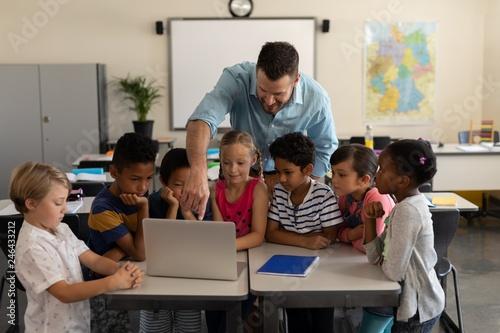 Fotomural Male teacher teaching kids on laptop in classroom