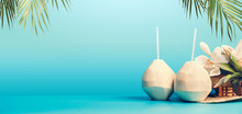 Summer Tropical Vacation Background Banner With Fresh Tropical Coconut Cocktails , Drinking Straws And Hanging Palm Leaves On Blue Turquoise Background. Travel And Holiday Concept