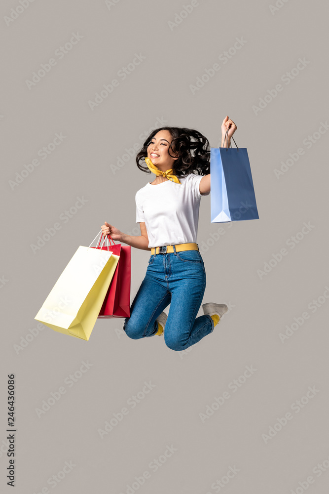 Fototapeta Excited asian woman holding colorful shopping bags and happily jumping with one raised hand isolated on grey