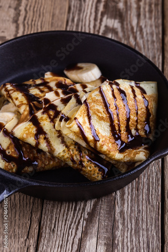 Crepes with bananas and chocolate topping for breakfast