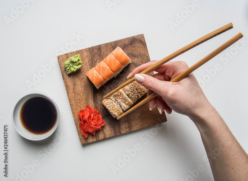 Fotografía  girl eating an appetizing sushi set with ginger, soy sauce and wasabi on a white