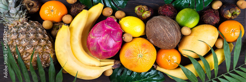Healthy rainbow tropical fruits banner with palm leaves on blue wooden table, top view, - 246444276