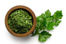 Dried Chopped Parsley In Dark Wood Bowl Next To Fresh Parsley Leaves Isolated On White From Above.