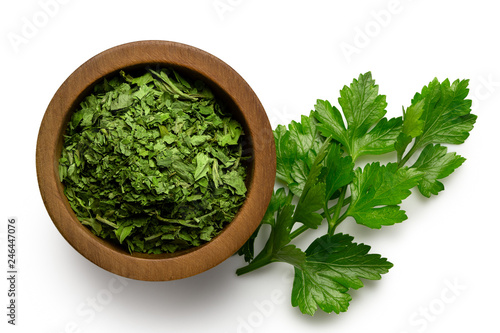 Fototapeta Dried chopped parsley in dark wood bowl next to fresh parsley leaves isolated on white from above. obraz