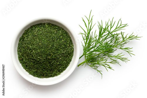 Fotomural Dried chopped dill in white ceramic bowl next to fresh dill leaves isolated on white from above