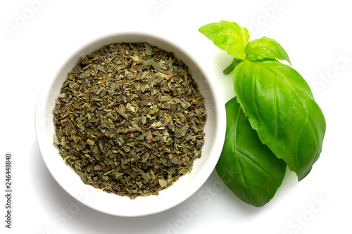 Canvastavla Dried chopped basil in white ceramic bowl next to fresh basil leaves isolated on white from above