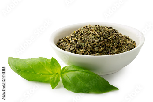 Fotografía Dried chopped basil in white ceramic bowl next to fresh basil leaves isolated on white