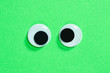 canvas print picture - Mad googly eyes on neon green background. Cross-eyed funny toys eyes close up.