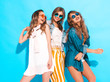 canvas print picture - Three young beautiful smiling hipster girls in trendy summer colorful clothes. Sexy carefree women in sunglasses isolated on blue. Positive models going crazy