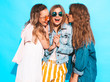 Three young beautiful smiling hipster girls in trendy summer casual clothes. Sexy women share secrets, gossip.Isolated on blue. Surprised face emotions