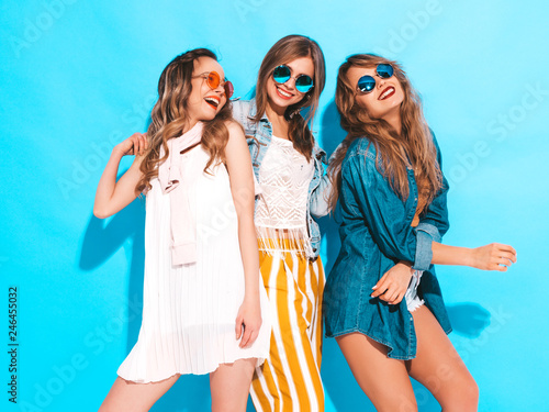 canvas print motiv - halayalex : Three young beautiful smiling hipster girls in trendy summer colorful clothes. Sexy carefree women in sunglasses isolated on blue. Positive models going crazy