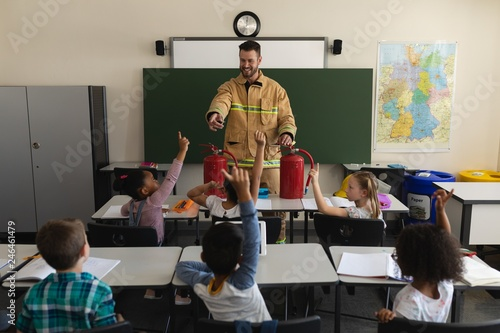 Schoolkids raising hands while male firefighter teaching about