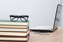Glasses On Stacked Books And Laptop