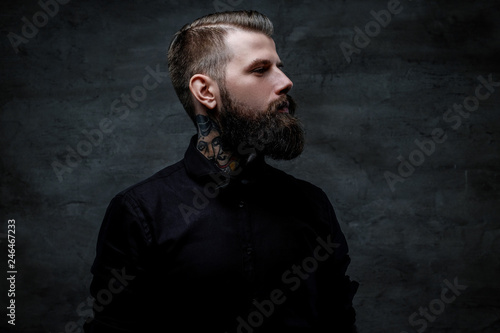 Fotografiet  Profile portrait of an expressive bearded man with tattoos on his neck