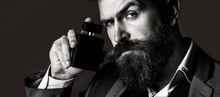 Man Holding Up Bottle Of Perfume. Man Perfume, Fragrance. Fashion Perfume Bottle. Businessman Likes Perfume Scent.