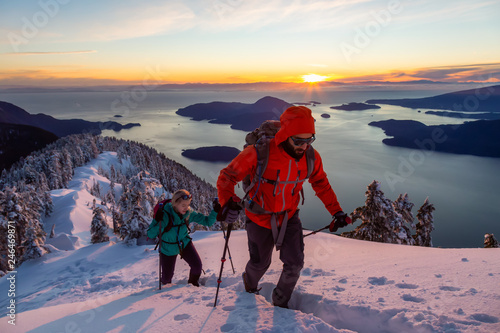 Adventure seeking man and woman are hiking to the top of a mountain during a vibrant winter sunset. Taken in Mnt Harvey, North of Vancouver, BC, Canada. - 246469871