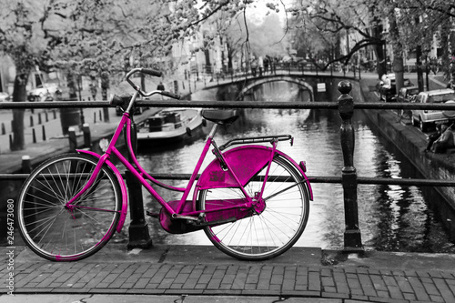 Fotobehang Fiets A picture of a lonely pink bike on the bridge over the channel in Amsterdam. The background is black and white.