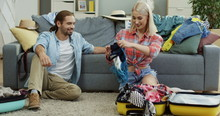 Charming Blonde Young Woman Packing Clothes In The Suitcase And Demonstrating To Her Young Just-married Husband While He Sitting On The Floor Next To Her And Smiling.