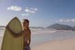 Female surfer standing with surfboard at beach