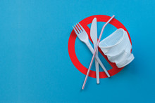 White Plastic Single Tableware On A Blue Background As A Symbol Of Environmental Pollution