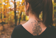 Tattoo On The Back Of A Young Girl With Reddish Hair Dressed In A Poncho In An Autumnal Forest