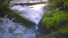 Rushing Water Rapids Running Through Log Chute And Crashing Into Damaged Moss Covered Log Chute Wooden Beams While Spraying Mist And Water Onto Moss-Covered Rocks And Green Vegetation 4K ProRes