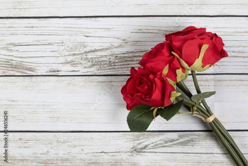 Fotografia  Roses on wooden board