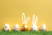 Decorated Easter Eggs And Cute Bunny's Ears On Green Grass Against Color Background. Space For Text