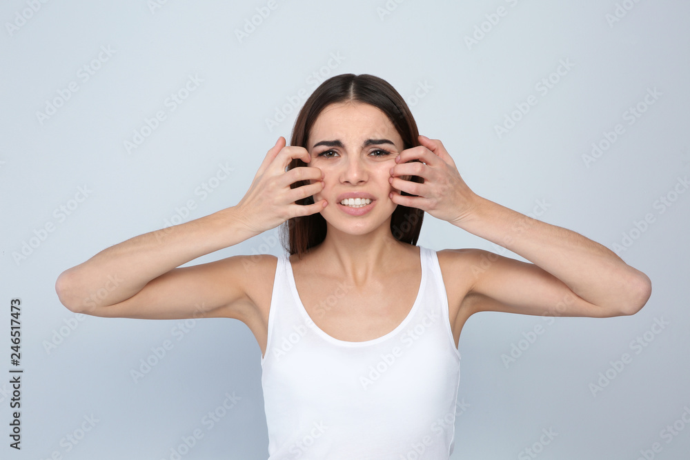 Fototapety, obrazy: Young woman scratching face on light background. Annoying itch