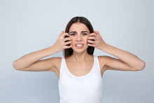 Young Woman Scratching Face On Light Background. Annoying Itch