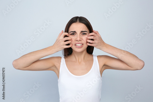 Obraz Young woman scratching face on light background. Annoying itch - fototapety do salonu