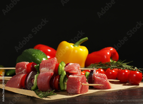 Skewers with fresh raw meat and vegetables on table against dark background