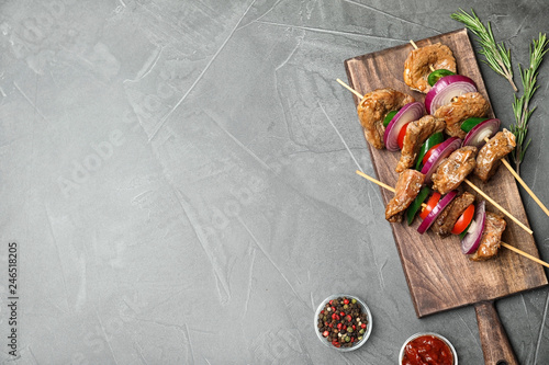 Roasted meat served with vegetables and sauce on grey background, flat lay. Space for text