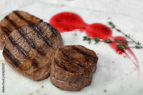 Grilled meat with sauce and thyme on light background, closeup