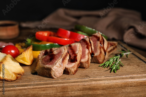 Cut roasted meat served with sauce and garnish on wooden board, closeup
