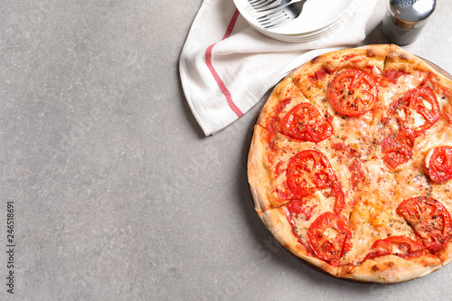 Hot cheese pizza Margherita on grey table, top view. Space for text