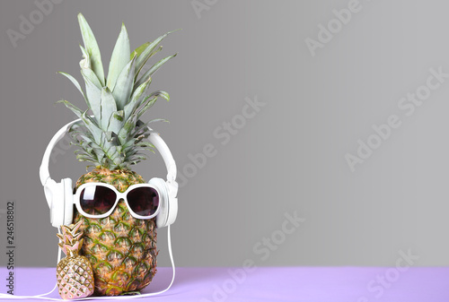 Pineapple with headphones and sunglasses on table against grey background. Space for text