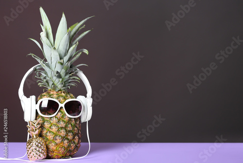 Pineapple with headphones and sunglasses on table against dark background. Space for text