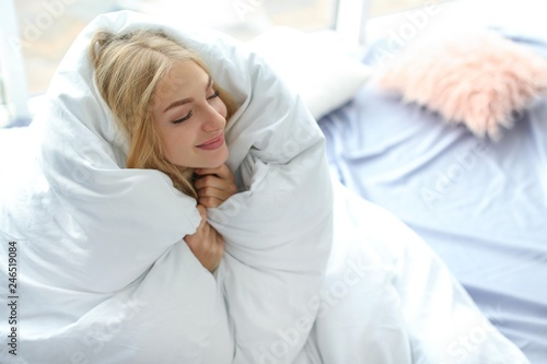 Fotomural  Beautiful young woman wrapped in soft blanket at home