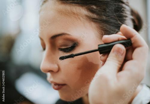 Makeup artist applying mascara onto the model Canvas Print