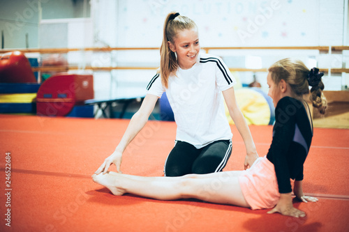 Spoed Fotobehang Gymnastiek Coach talking with a young gymnast